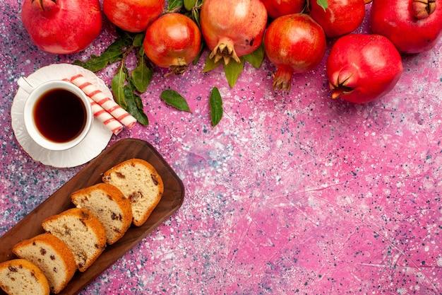Vue de dessus des grenades rouges fraîches avec un gâteau en tranches et une tasse de thé sur un bureau rose