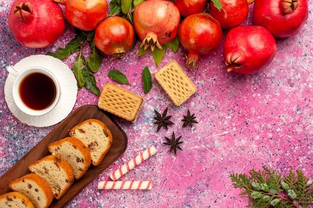 Vue de dessus des grenades rouges fraîches avec des gaufres de gâteau en tranches et une tasse de thé sur un bureau rose