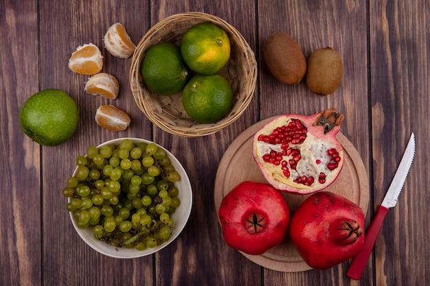 Vue de dessus des grenades sur un support avec des mandarines vertes et des raisins dans un panier sur une table en bois