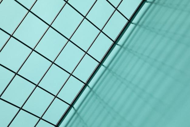 Vue de dessus d'une grille métallique coulant des ombres sur un fond cyan