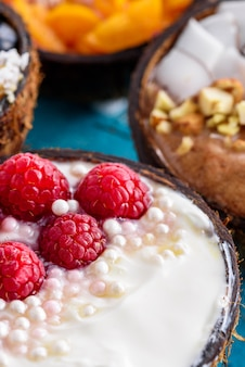 Vue de dessus gros plan bols de smoothie colorés avec framboises, noix, mangue congelée dans des bols de noix de coco sur fond bleu