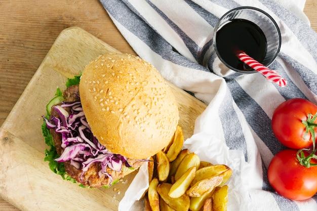 Vue de dessus gros plan de burger et frites sur une planche de bois