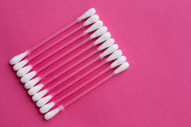 Vue de dessus gros plan sur des coton-tiges disposés en diagonale sur fond rose