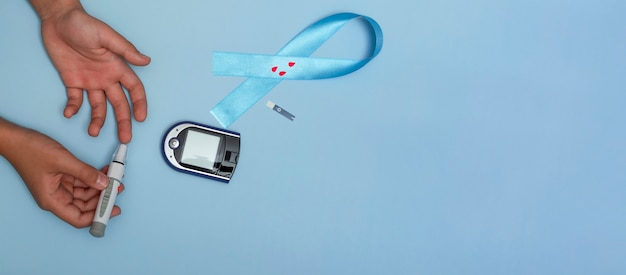 Vue de dessus en gros plan du concept pour la journée mondiale du diabète le 14 novembre. l'enfant mesure la glycémie sur fond bleu et un ruban bleu avec des gouttes de sang. bannière