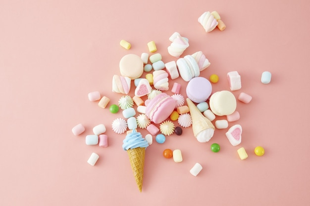 Vue de dessus en gros plan de guimauves colorées, macarons isolés sur un mur rose