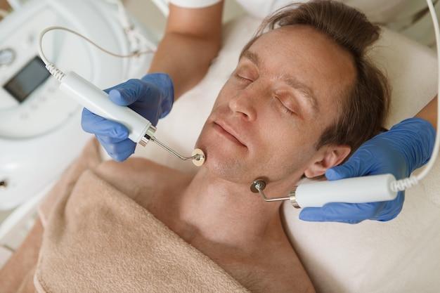 Vue de dessus gros plan d'un homme mûr détendu bénéficiant d'une procédure de soin du visage par cosméticienne