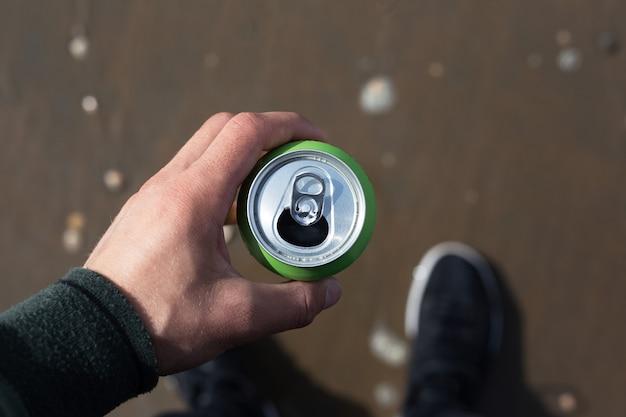 Vue de dessus, gros plan d'un homme tenant une canette de soda sur la plage.