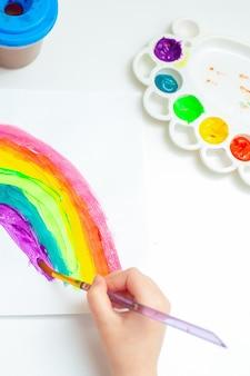Vue de dessus en gros plan d'une main d'enfant dessinant un arc-en-ciel sur le papier blanc. un enfant peint à la maison.
