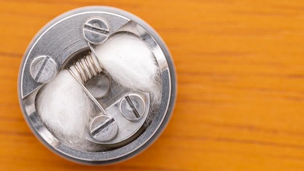 Vue de dessus, gros plan, photo macro d'une bobine à espace unique avec une mèche en coton biologique japonais dans un atomiseur dégoulinant reconstructible haut de gamme pour chasseur de saveurs, dispositif de vapotage, mise au point sélective