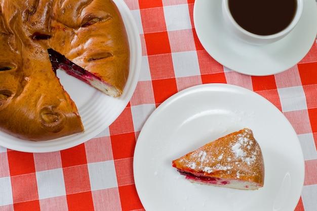 Vue de dessus en gros plan photo de tarte aux cerises et tasse de thé sur nappe à carreaux
