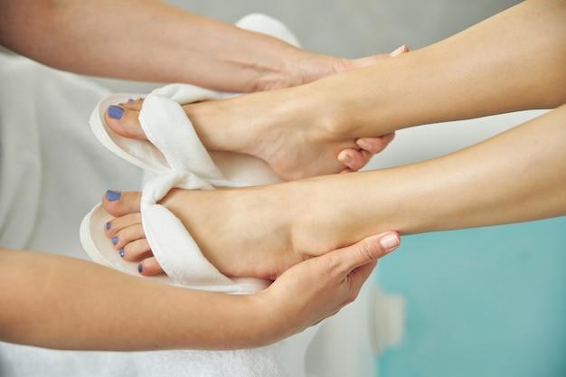 Vue de dessus gros plan des pieds de femme en tongs blanches massées par un professionnel dans un salon de spa