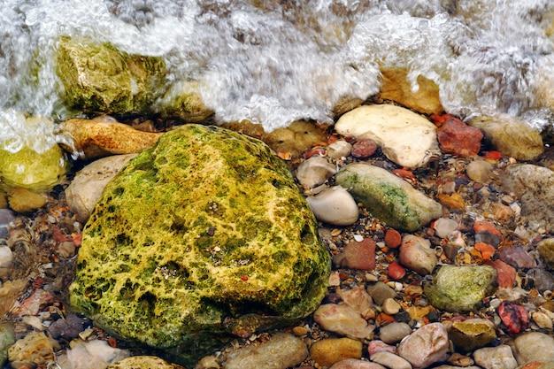 Vue de dessus de gros rocher vert sur la plage à côté de petits colorés