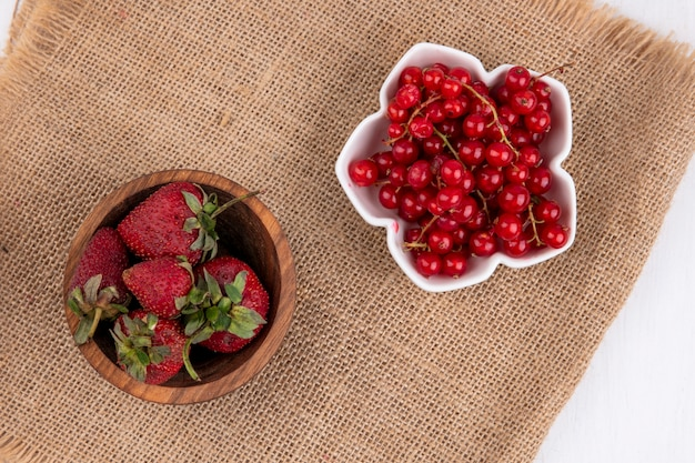 Vue de dessus de groseille rouge dans un bol avec des fraises sur une serviette beige