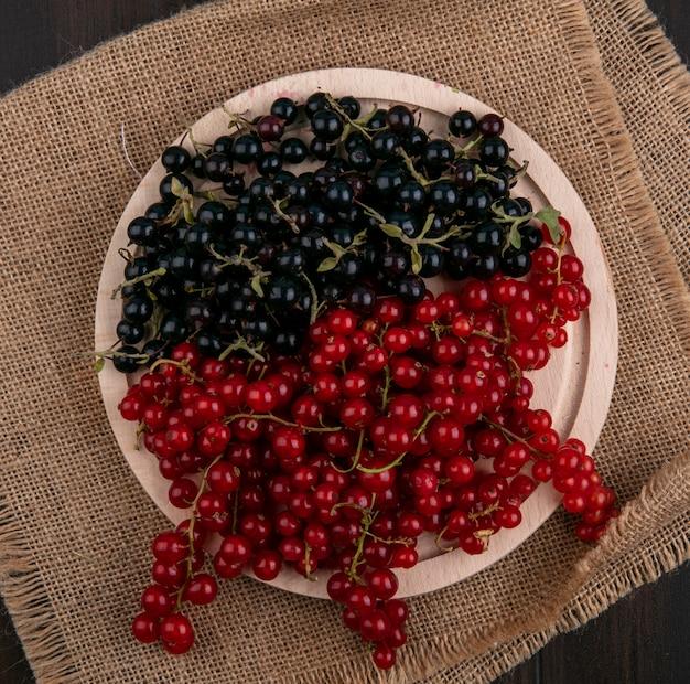 Vue de dessus groseilles rouges et noires sur une assiette sur une serviette beige