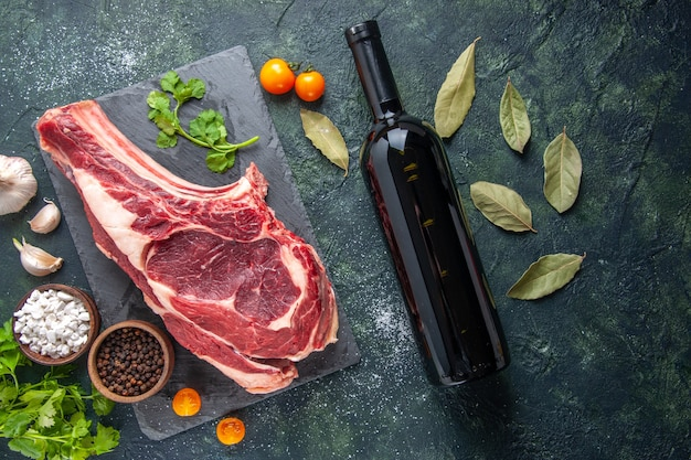 Vue de dessus grosse tranche de viande viande crue avec du poivre et des verts sur une surface sombre