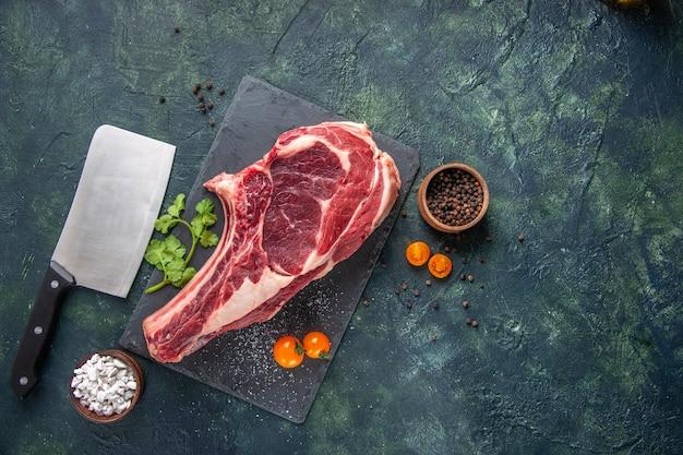 Vue de dessus grosse tranche de viande viande crue avec des verts sur une surface sombre
