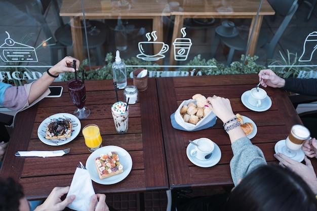Vue de dessus d'un groupe d'amis prenant le petit déjeuner dans un café en plein air.