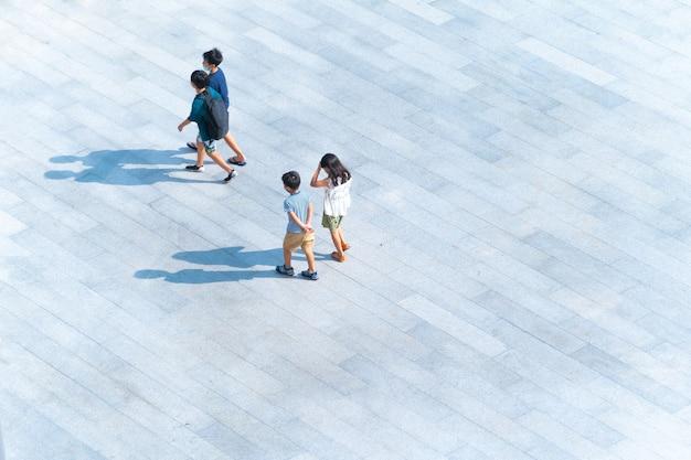 Vue de dessus groupe d'enfants et d'enfants marchant sur une passerelle piétonne en plein air pour voyager