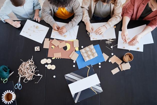Vue de dessus d'un groupe d'enfants fabriquant des modèles en carton pendant les cours d'art et d'artisanat à l'école avec une enseignante, espace de copie
