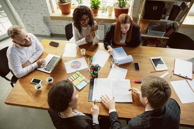 Vue de dessus. groupe de jeunes professionnels ayant une réunion. un groupe diversifié de collègues discute de nouvelles décisions, plans, résultats, stratégie. créativité, lieu de travail, affaires, finance, travail d'équipe.