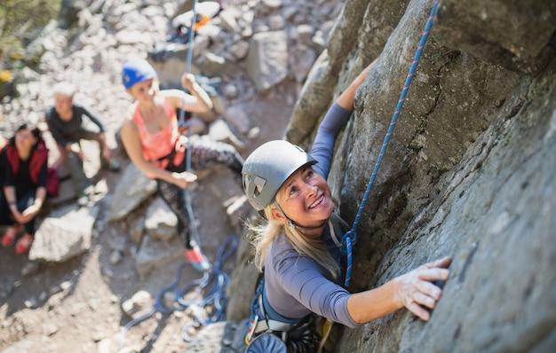 Une vue de dessus d'un groupe de personnes âgées avec un instructeur qui escalade des rochers à l'extérieur dans la nature, un mode de vie actif.