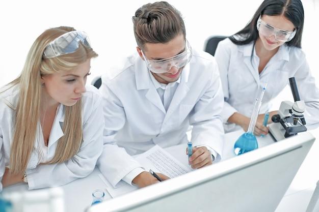 Vue de dessus un groupe de scientifiques travaillant sur un ordinateur dans le laboratoire. science et santé