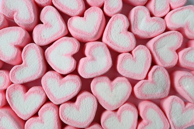 Vue de dessus de guimauve en forme de coeur rose et blanc pastel pour le fond