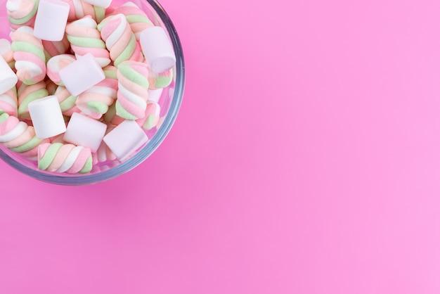 Une vue de dessus des guimauves blanc-rose sucrées et collantes sur rose