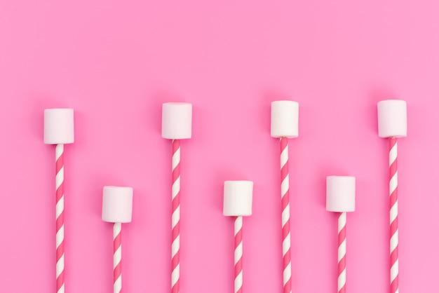 Une vue de dessus des guimauves blanches avec des bâtons roses sur un bureau rose, couleur sucrée de sucre