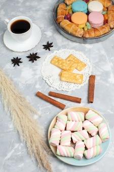 Vue de dessus des guimauves et du thé avec des bagels et des macarons sur un bureau blanc