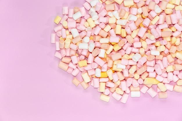 Vue de dessus sur les guimauves multicolores sur fond rose monochrome