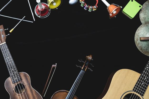 Vue de dessus de guitare violon et ukulélé avec instruments à percussion sur le fond noir