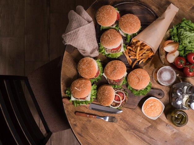 Vue de dessus des hamburgers avec de la viande de boeuf à côté des frites. table en bois. fromage fondu.