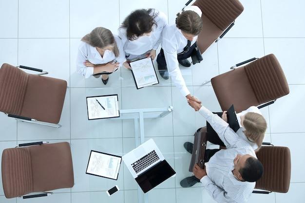 Vue de dessus.handshake partenaires financiers avant la réunion d'affaires .photo avec espace de copie