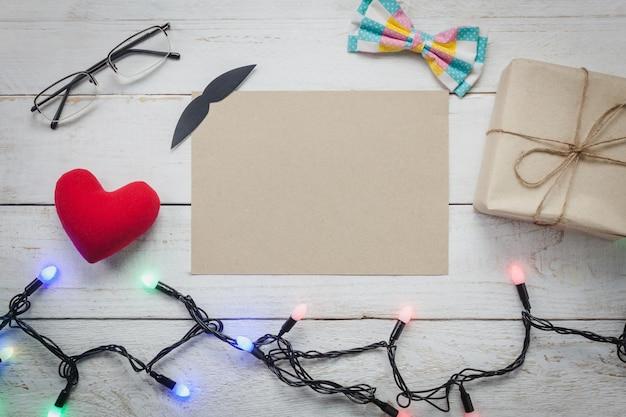 Vue de dessus happy father day.blank paper pour un espace de texte gratuit sur fond de bois rustique.accessoires avec, lumières, cadeaux, moustaches, cravates vintage, lunettes, présents, coeur rouge.