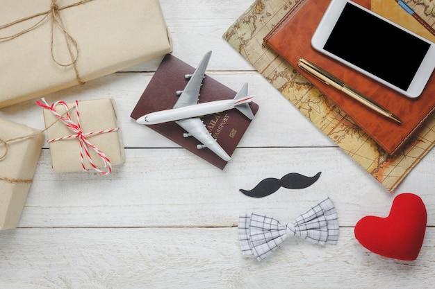 Vue de dessus happy father day with travel.airplane et passeport sur fond de bois rustique.accessoires avec, carte, moustache, cravate vintage, stylo, cadeau, coeur rouge, téléphone portable et cahier blanc.