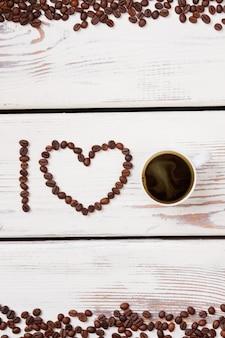 Vue de dessus des haricots arrangés et une tasse de café. planches de bois blanches.