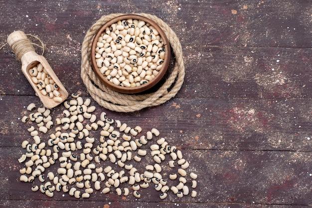 Vue de dessus des haricots crus frais à l'intérieur et à l'extérieur du bol brun répartis sur tout le haricot brun, haricot cru alimentaire