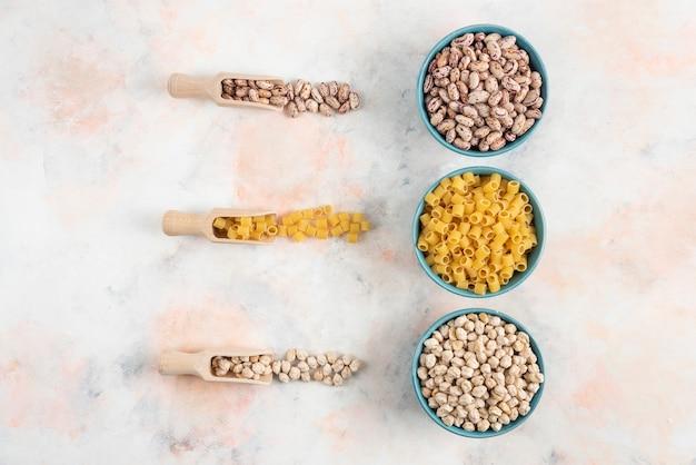 Vue de dessus haricots, pâtes et pois chiches dans un bol sur une surface blanche.