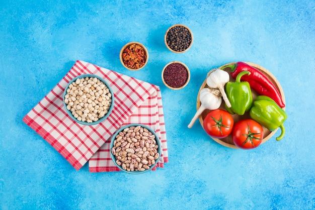Vue de dessus des haricots et des pois chiches dans un bol et des légumes frais avec des épices sur fond bleu.