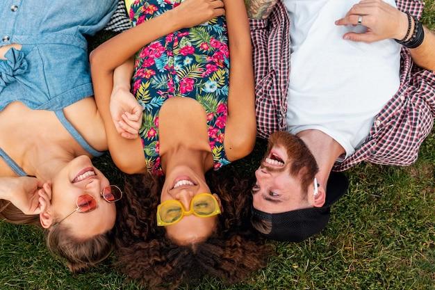 Vue de dessus d'en haut sur l'élégant coloré jeune entreprise heureuse d'amis allongé sur l'herbe dans le parc, l'homme et la femme s'amusant ensemble