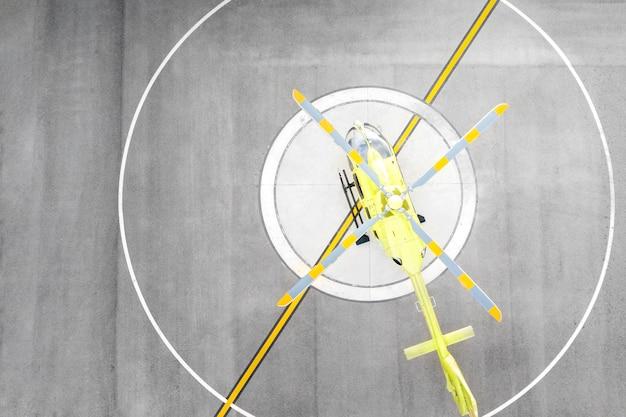 Vue de dessus de l'hélicoptère jaune sur l'héliport