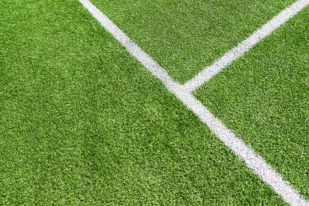 Vue de dessus de l'herbe verte de terrain de football de football artificiel avec ligne blanche