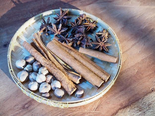Vue de dessus des herbes et épices séchées sur un panier de tissage en bambou sur une table en bois.