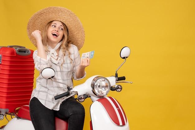 Vue de dessus de l'heureuse jeune femme portant un chapeau et assis sur une moto et tenant un billet sur jaune
