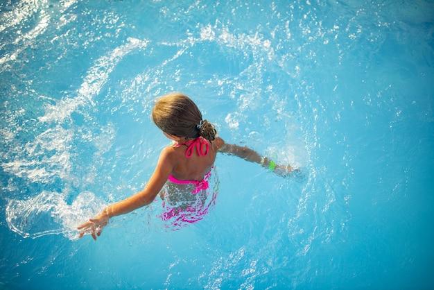 Vue de dessus heureuse petite fille en maillot de bain de couleur vive nage dans l'eau claire et chaude de la piscine journée d'été ensoleillée pendant les vacances. concept de vacances et de tourisme en famille.