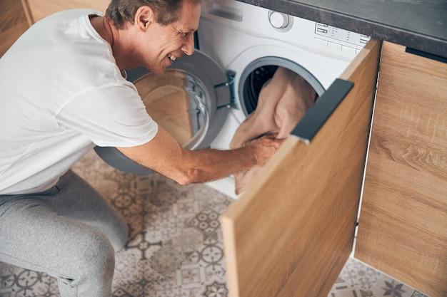 Vue de dessus d'un homme adulte heureux et heureux debout près de la laveuse tout en mettant des vêtements à l'intérieur de la machine