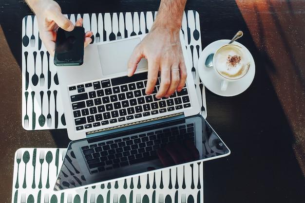 Vue de dessus d'homme d'affaires à l'aide d'un ordinateur portable et d'un téléphone intelligent alors qu'il travaillait au café