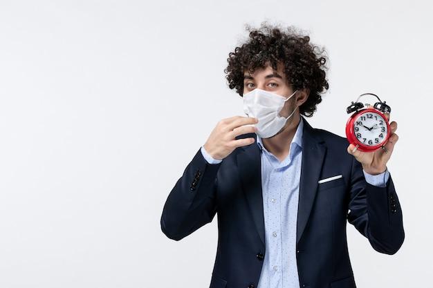 Vue de dessus d'un homme d'affaires en costume et portant son masque tenant une horloge dans des pensées profondes
