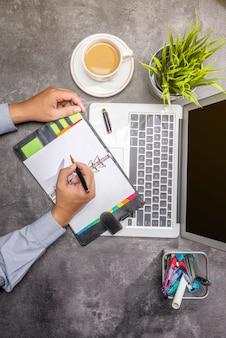 Vue de dessus d'homme d'affaires écrivant dans le bloc-notes avec ordinateur portable, café, plante en pot et accessoires